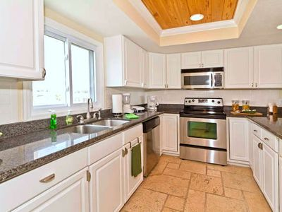 Bright Kitchen highlighted by tile floor and recessed lighted cieling