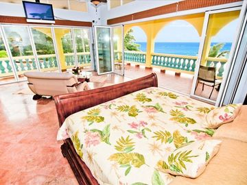 The glass walls open up for breathtaking ocean views past the spacious lanai!