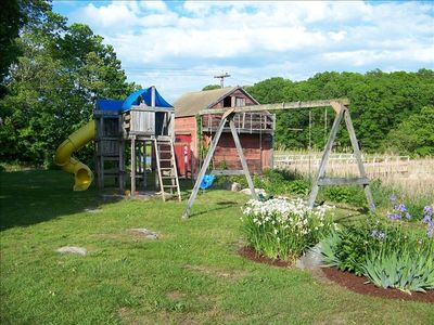 Playground with two towers, curly slide and and swing set overlooking river