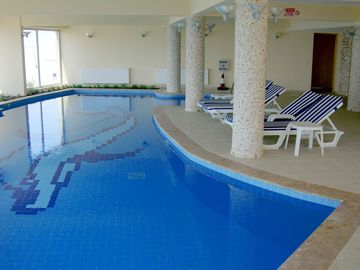Indoor heated communal pool with sun loungers