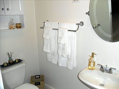 Bathroom sink, toilet, towels, Mirror, storage.