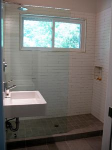 Guest bathroom. Light filled with full size open shower and rain shower head