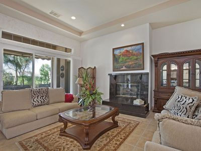 Formal living room with full view of pool, golf course & mountains