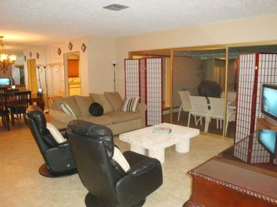 Living room opens to pool deck & features queen size sleeper sofa and HDTV.