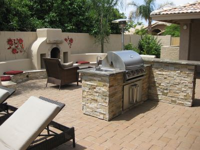 backyard patio with BBQ, outdoor fireplace, wicker lounge chairs/sofa, pool,spa