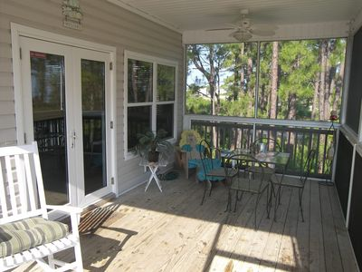 front screened porch with view of bay across the street