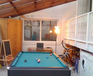 Sun room with 2 bikes, washer dryer and pool table