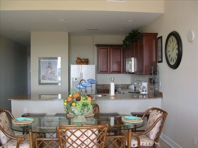 Kitchen, bar w/ 4 stools, dining table & chairs...open to living room & views