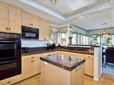 Gourmet kitchen with ocean view and flat screen TV.