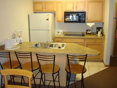 Breakfast bar, refrigerator, stove top burner, dishwasher and essentials
