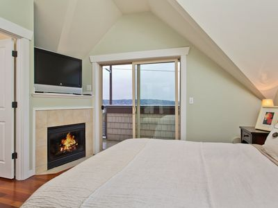 Master bedroom with fireplace opens onto balcony with Olympics view