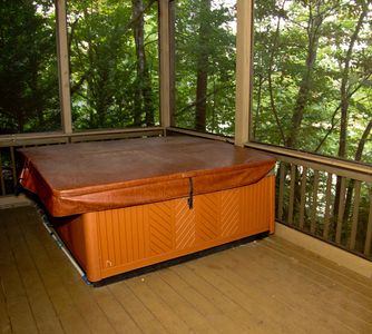 Hot tub on lower deck that is screened