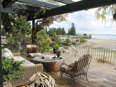 The covered deck looks out over the beach at low tide.