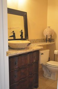 The vanity matches the kitchen with granite but introduces old world styles.