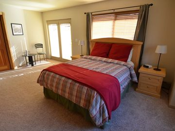 Bedroom with queen size bed and door to outdoor deck