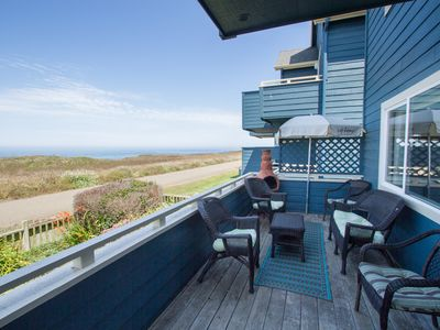 Oceanview downstairs patio with BBQ grill, seating area, and fenced garden yard