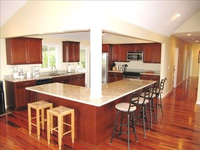 Large kitchen with granite counters,rotating stools and Tiger Wood floors.
