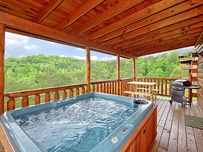 Hot tub on open deck with wooded views gas grill and picnic table