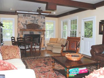 Great room with projection screen TV, game table and fireplace.
