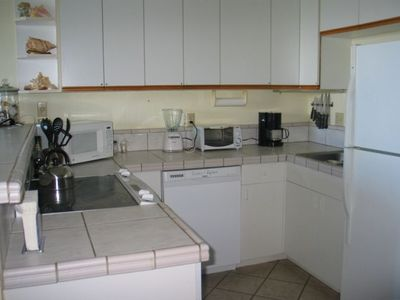 Fully equipped kitchen with tile counters, ceramic top stove and tile floors.