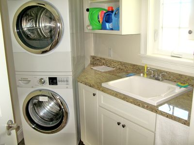 separate laundry room with high end large capacity Bosch washer and dryer