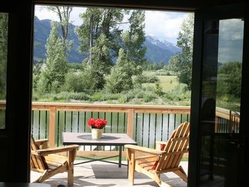 Jackson Hole cabin rental - inviting view from inside of the deck, pond and Tetons.