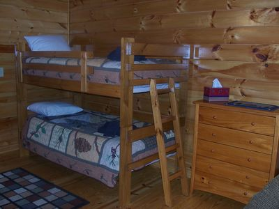 Main level bedroom has set of bunks and queen bed and twin sleeper loveseat