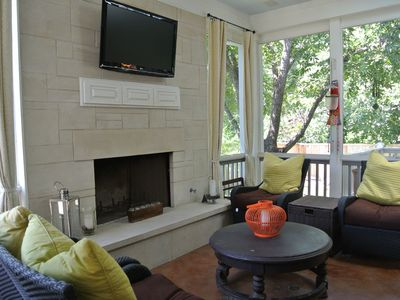 Screened in outdoor living room with fireplace and television.