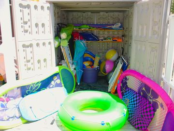 Stocked shed in backyard full of pool and beach equipment.