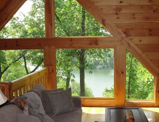 "Lake Lure cabin photo - Loft with ""treetop"" picture window views of the lake, sofa bed, chair, desk"