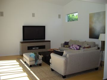 Media room with 56' flat screen TV and casual seating. Overlooks pool.