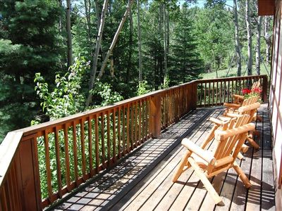 Front deck with cedar furniture and view of aspens, firs, and spruce trees