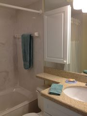 Fort Myers Beach condo photo - Guest bathroom- Marbled Tub/Shower- Quartz countertop- Wrap around mirror