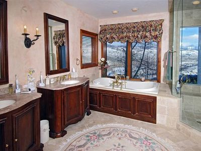 "A shower and tub with a ""top of the world"" view."