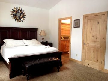 Master bedroom w/ King size bed. Door to walk-in closet on right. Attached deck.