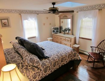 Master Bedroom w/ queen bed, A/C unit, ceiling fan, skylight, TV, large closets