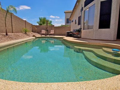 Large Private Pool with Lounge Chairs and Patio Furniture.