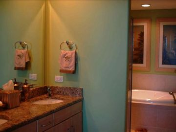 Master Bath w/ jacuzzi and glass shower, walk in closet & granite double sink