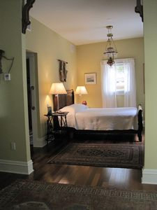 Master bedroom with hardwood floors, antiques and queen size bed.