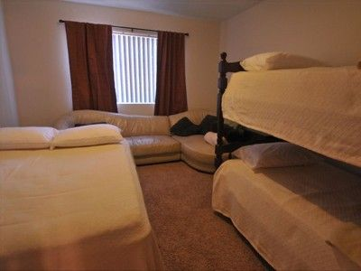Master bedroom with bunk bed, leather couch and a double bed
