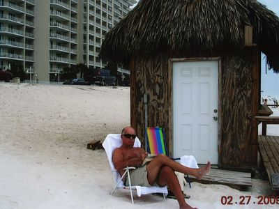 pops enjoying a cold drink at the tiki bar on the beach