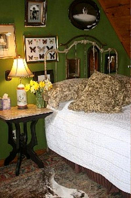 master bedroom with down comforter, cow skin rug and stuffed mountain lion.