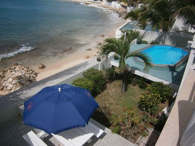 Aerial view of beach, pool & deck, tiled patio with table and umbrella & garden.