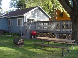 Howard Lake cabin photo - Outside front deck Fire pit, grill etc. Chairs and table on deck as well.