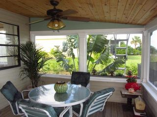 Merritt Island house photo - Outdoor table under covered porch by pool