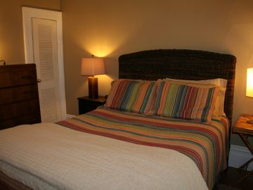 Comfortable bedroom with queen bed, two night stands, dresser and closet.