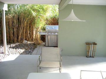 the patio with the large grill by the bamboo