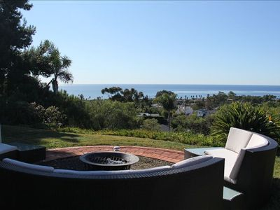 West backyard with outdoor couch and fire pit facing the ocean