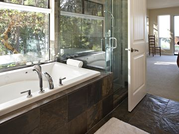 Master ensuite jetted tub overlooking green space and slate shower