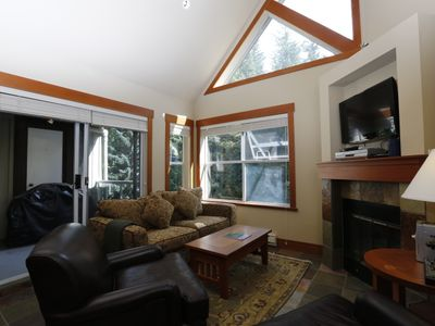 Bright condo with large windows and vaulted ceilings. Living room opens to patio